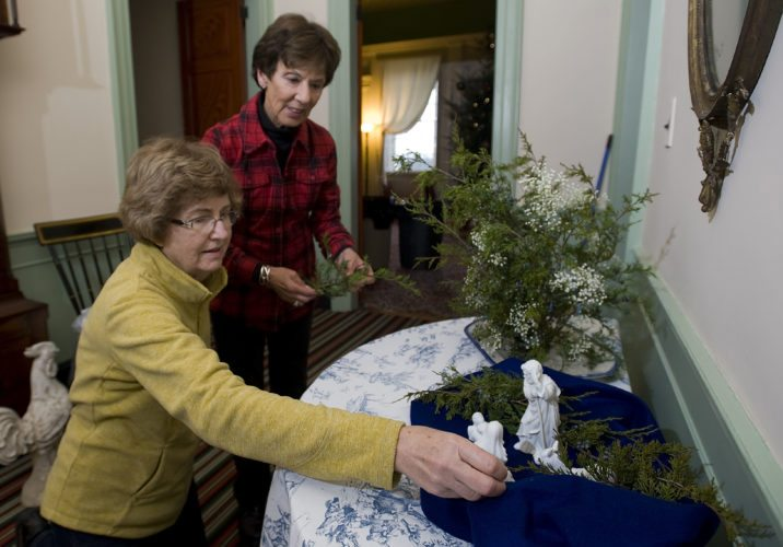 "Sue Cobb, left, and Jeane Eastham, right, both members of Valley Garden Club in Front Royal, decorate the foyer inside Belle Grove mansion in Middletown on Wednesday. Area garden clubs decorated rooms in the mansion,  with each creating decorations for the ""Christmas Around the World"" theme. Rich Cooley/Daily"
